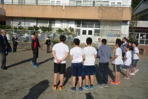 子どもたちから英語でルール説明を受けるヤレド選手